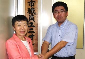 書記局の前で握手する「あいはらくみこ」さん(左)と津森委員長(右)